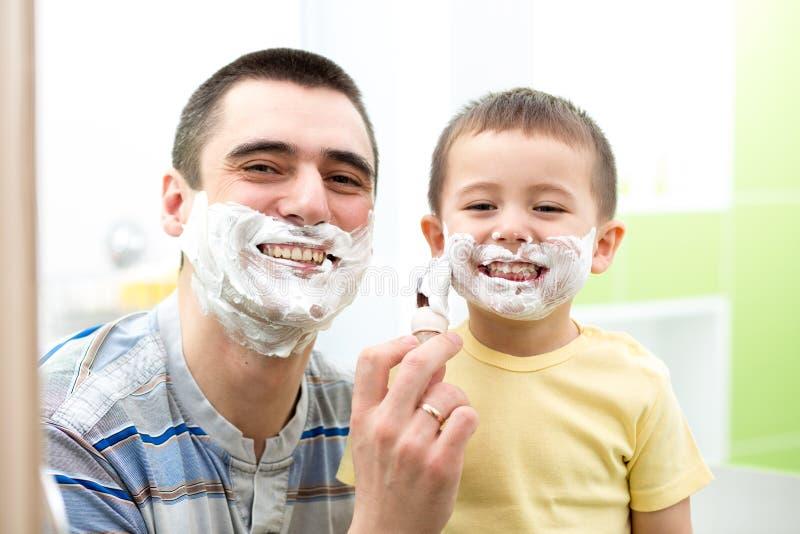 Gene ensinando a seu menino do filho como barbear fotografia de stock