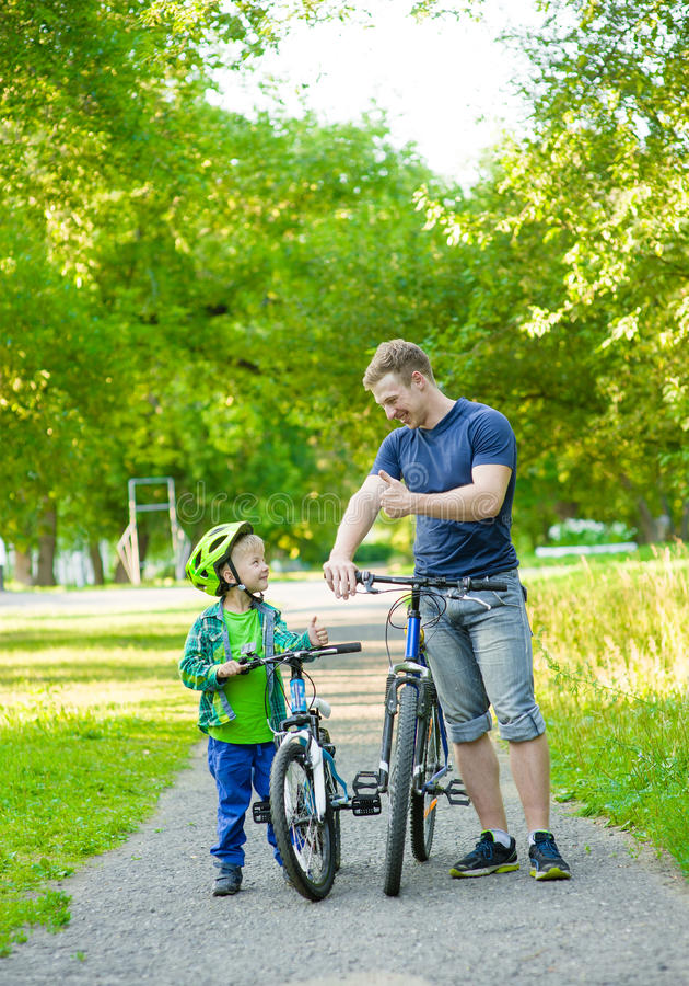 Gene a fala com seu filho que monta uma bicicleta imagens de stock royalty free