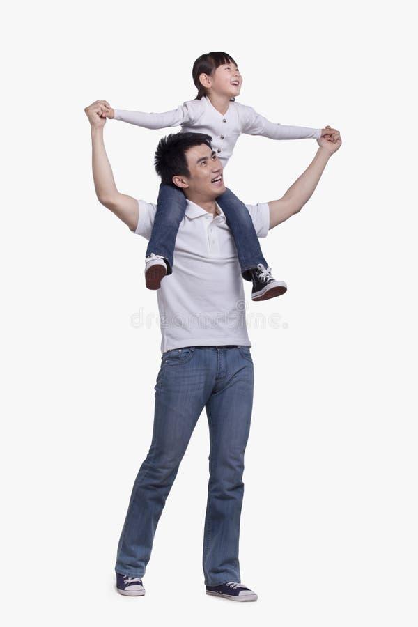 Gene a filha levando em seus ombros, tiro do estúdio imagem de stock