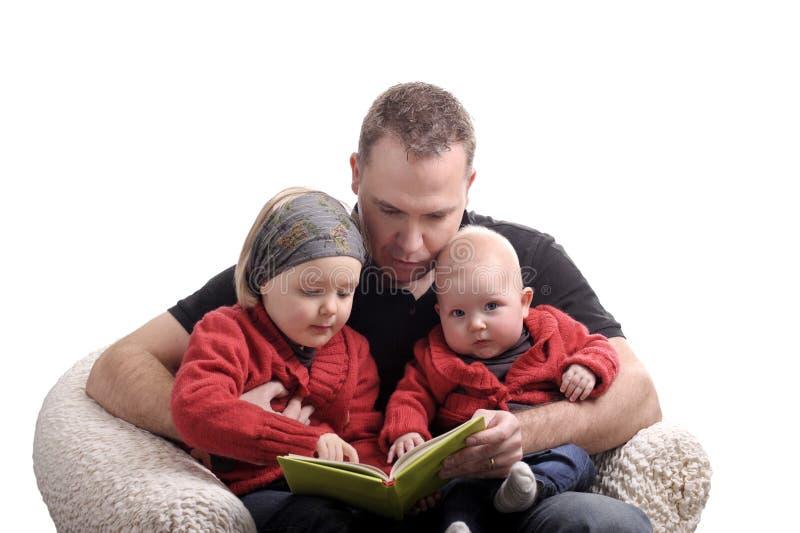 Gene a leitura de uma história em suas duas filhas pequenas imagens de stock