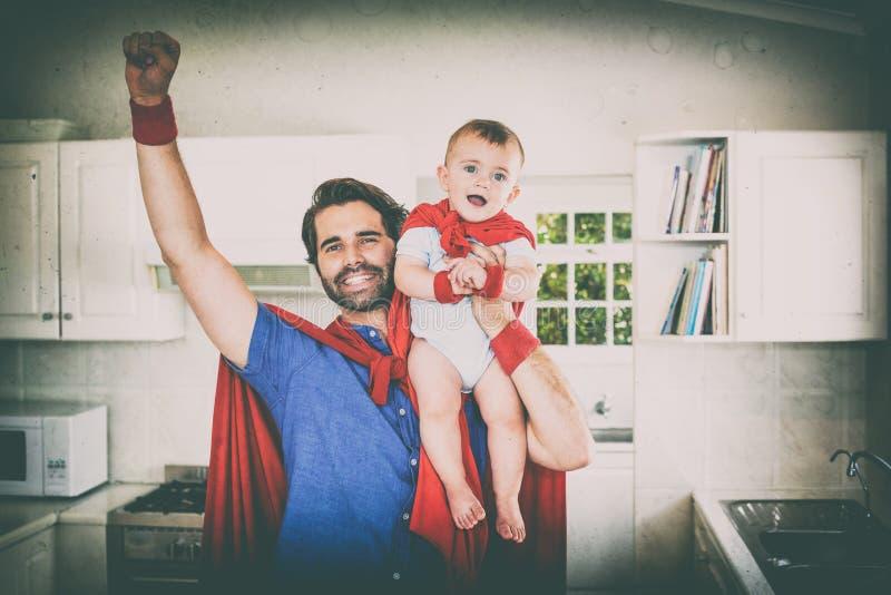 Gene no filho de levantamento do traje do super-herói na cozinha foto de stock
