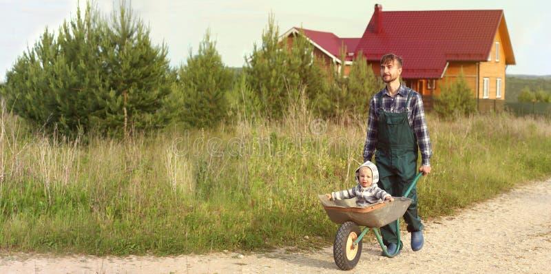 Gene no uniforme de trabalho que empurra o filho no carrinho de mão em uma estrada rural perto da casa da exploração agrícola Con fotografia de stock royalty free