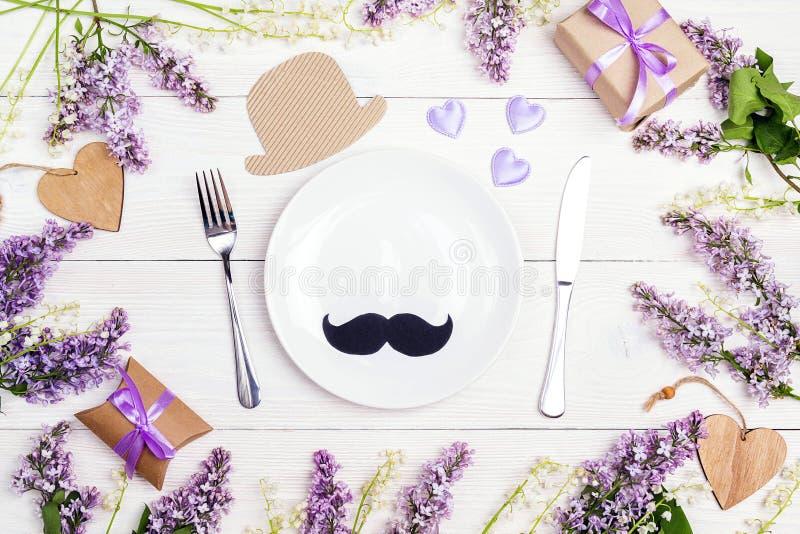 Gene o ajuste da tabela do dia do ` s com as flores da cutelaria e da mola no wh imagem de stock