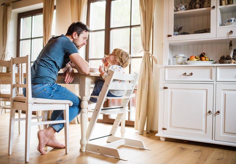 Gene o assento na tabela com um menino da criança em casa imagens de stock royalty free