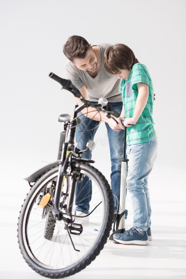 Gene o filho de ensino para bombear acima o pneu da bicicleta no branco imagem de stock royalty free
