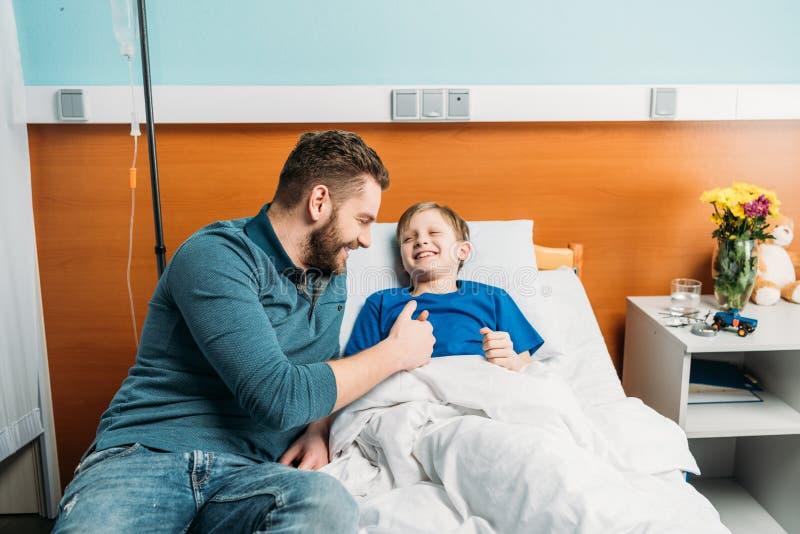 Gene o jogo com o filho pequeno bonito que encontra-se na cama, no paizinho e no filho de hospital no hospital imagem de stock
