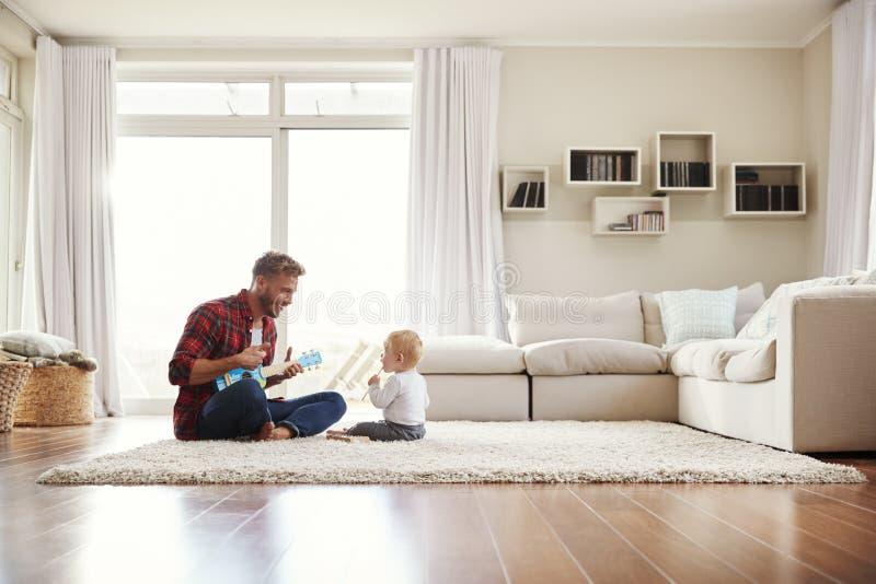 Gene o jogo da uquelele com o filho novo em sua sala de estar foto de stock