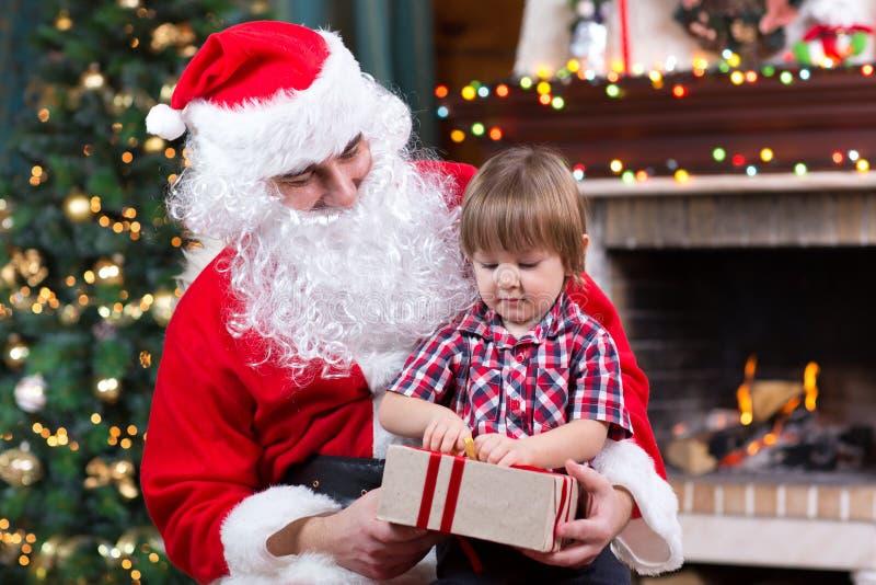 Gene o presente aberto weared do menino de Santa Claus e da criança que senta-se próximo pela árvore de Natal na chaminé imagem de stock