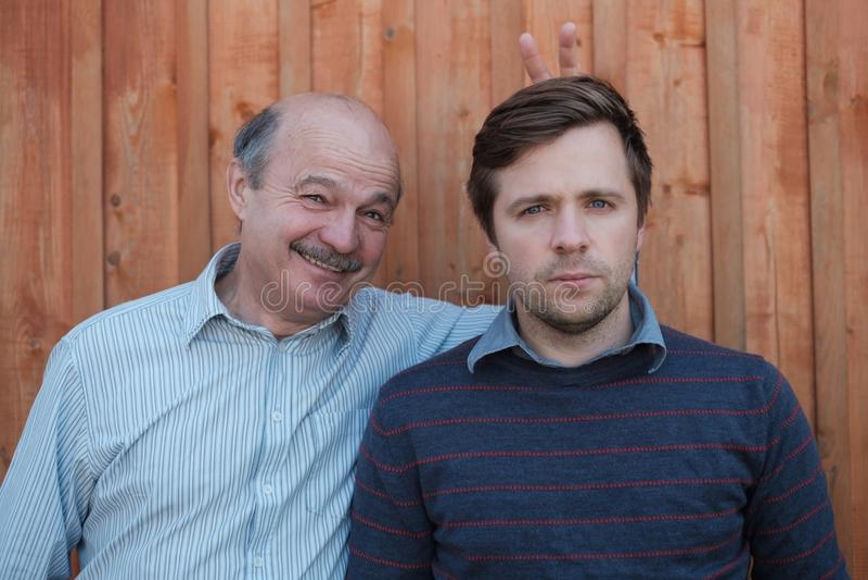 Gene pranking seu filho com as orelhas do coelho no fundo de madeira fotos de stock