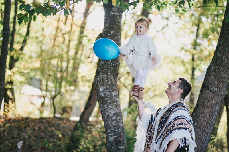Gene ter o divertimento com sua filha pequena em uma floresta do outono fotografia de stock royalty free