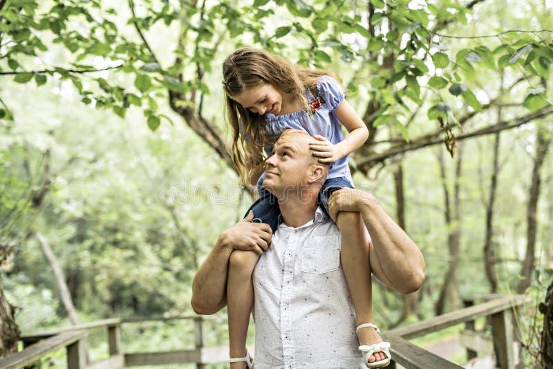 Gene ter o divertimento na floresta com sua filha em seu ombro imagem de stock