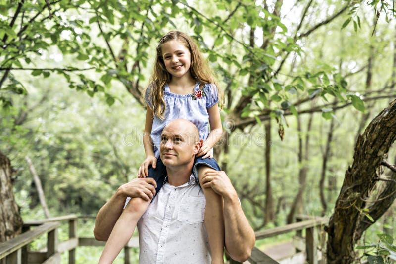Gene ter o divertimento na floresta com sua filha em seu ombro imagens de stock royalty free