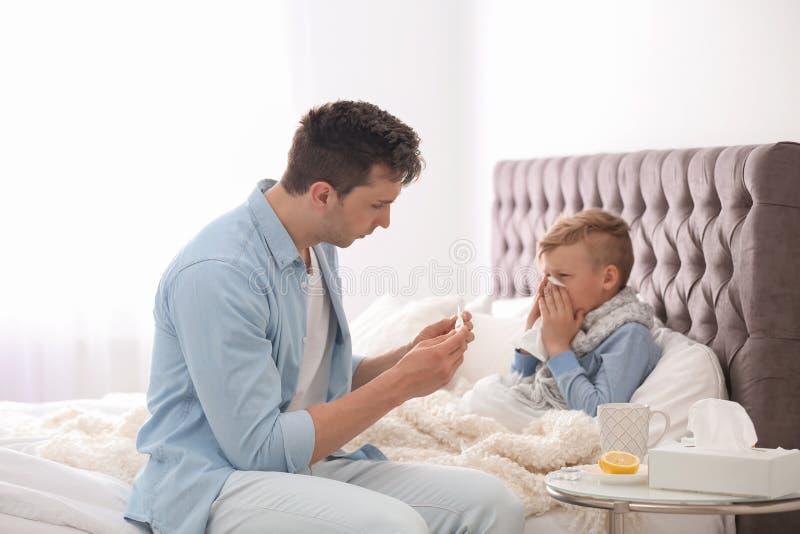 Gene tomar do filho pequeno que sofre do frio foto de stock royalty free