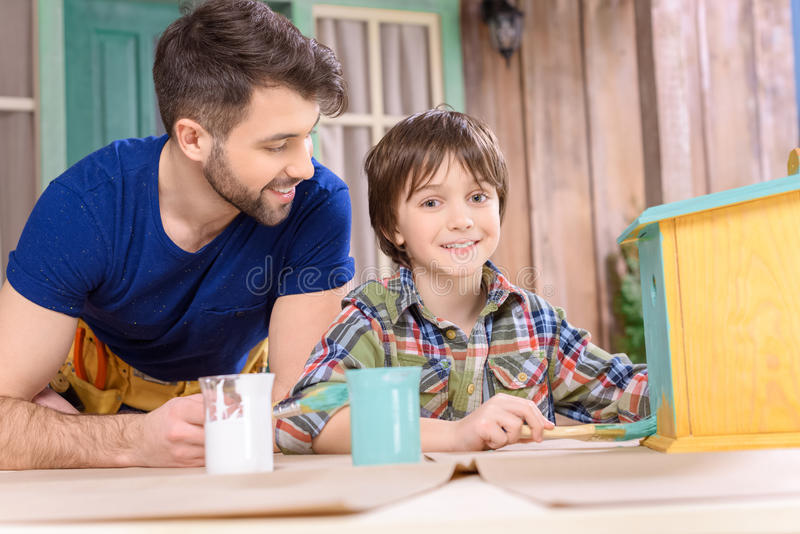 Gene a vista do filho que pinta o aviário de madeira e que sorri na câmera imagens de stock royalty free