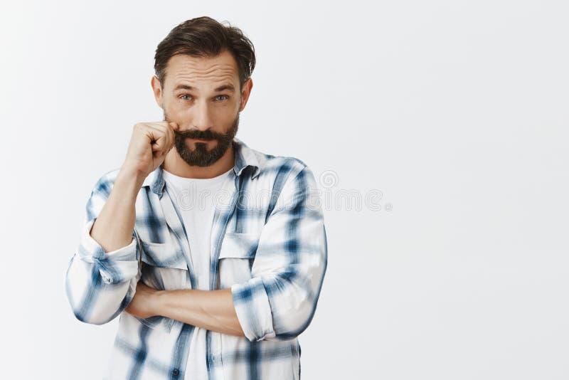 Gene a vista suspiciously no filho que veio tarde, fazendo estranho acusa Homem maduro atrativo de Dubtful com barba fotografia de stock
