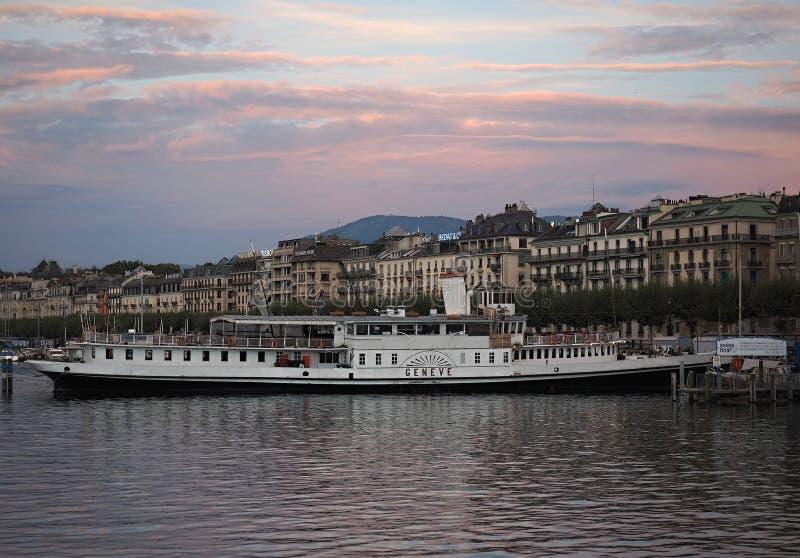 Genebra - Bela visão do pôr do sol no porto, onde no fundo está um barco interessante e parte da cidade antiga imagem de stock royalty free