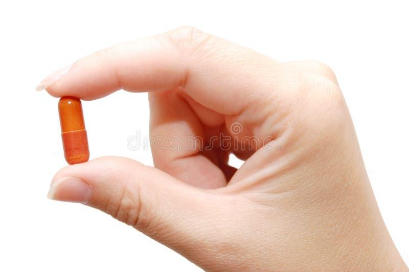 Geneeskunde in een hand op witte achtergrond stock afbeelding
