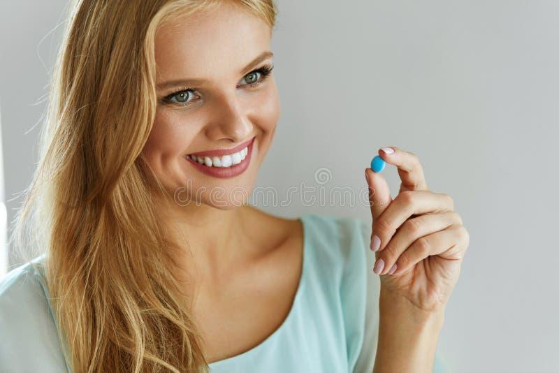 geneeskunde Mooie Glimlachende Vrouw die Medicijnpil nemen stock afbeeldingen