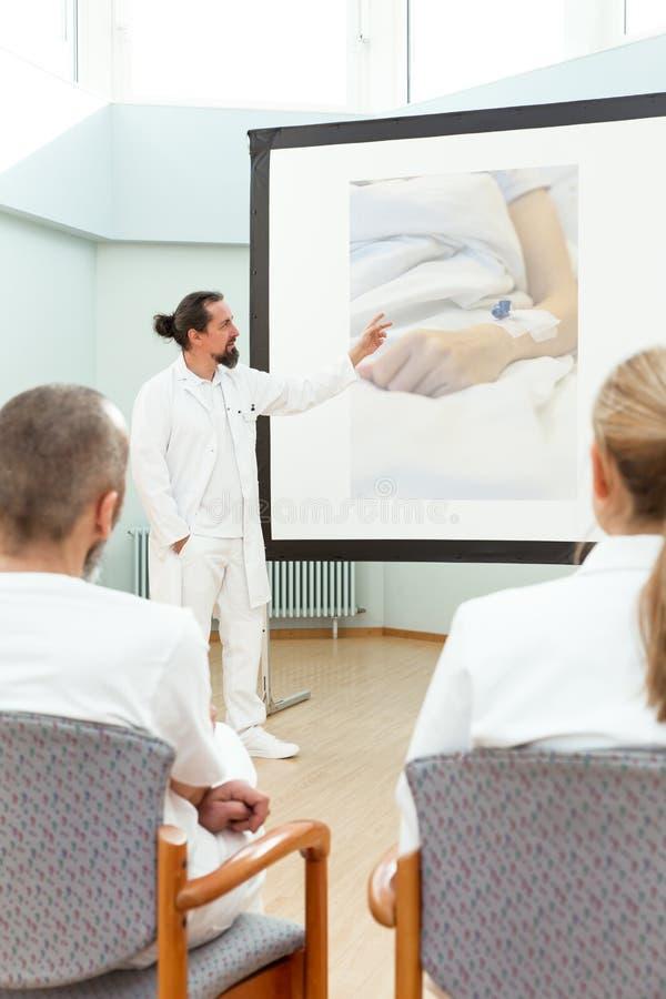 Geneeskundepersoneel die een vergadering hebben stock fotografie