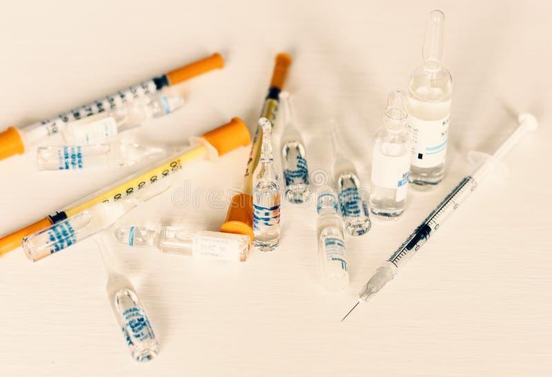 Geneeskundepillen of capsules met ampullen en spuiten op witte achtergrond met exemplaarruimte royalty-vrije stock afbeelding