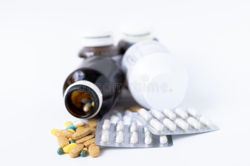 Geneeskundepillen, tabletten en capsules die uit pillenfles morsen op witte achtergrond stock foto