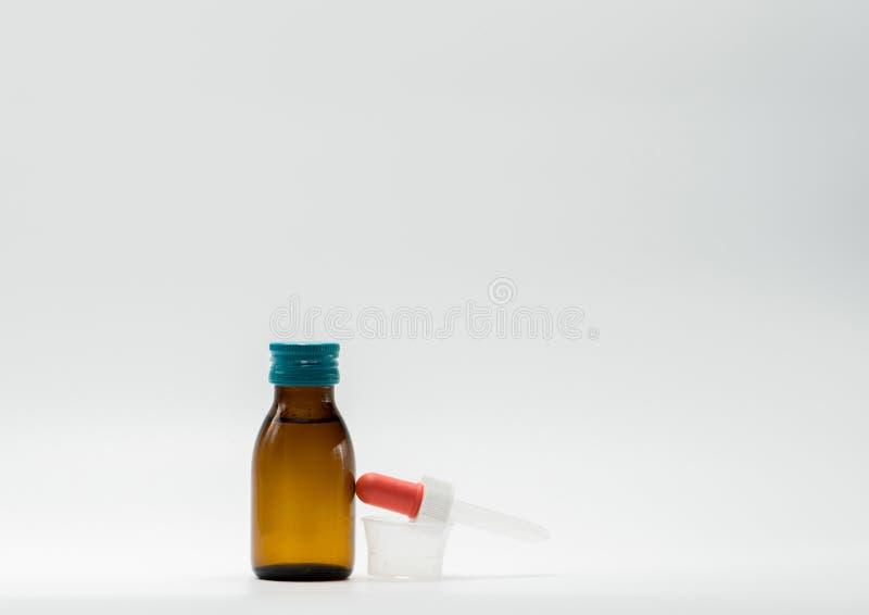 Geneeskundestroop in amberfles met leeg etiket en een plastic metende kop, druppelbuisje royalty-vrije stock afbeeldingen