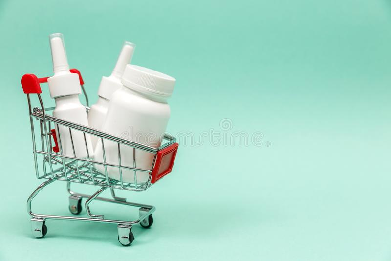 Geneesmiddelen in boodschappenwagentje op blauwe achtergrond royalty-vrije stock afbeeldingen