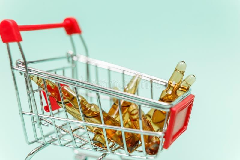 Geneesmiddelen in boodschappenwagentje op blauwe achtergrond royalty-vrije stock foto