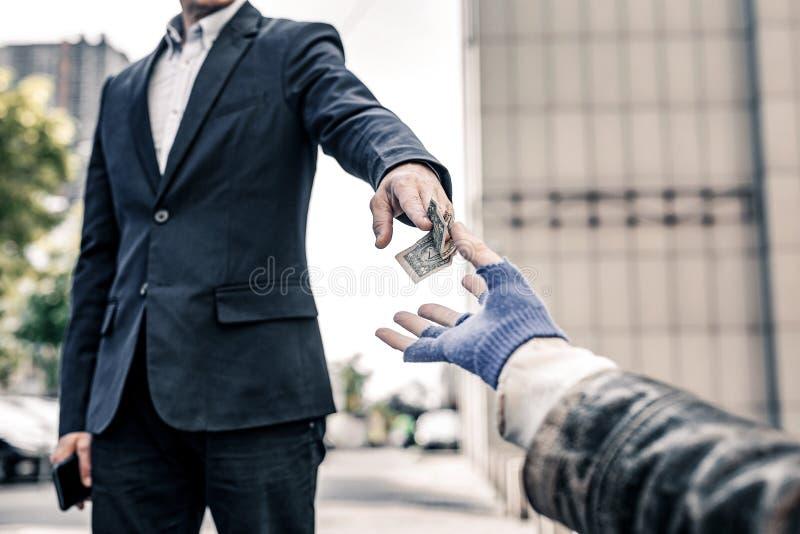Generös snygg man i mörk dräkt som delar hans pengar med hemlös arkivfoton