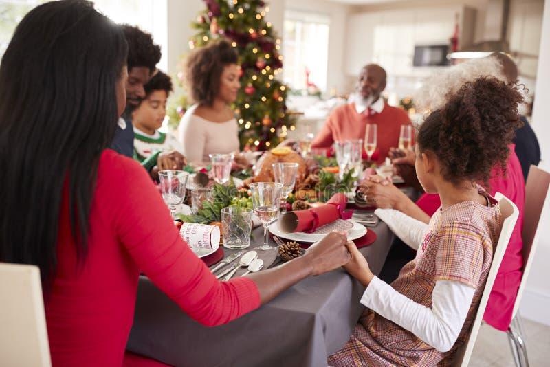 Generación multi, familia de la raza mixta que lleva a cabo las manos y que dice la tolerancia en la tabla de cena de la Navidad, fotos de archivo
