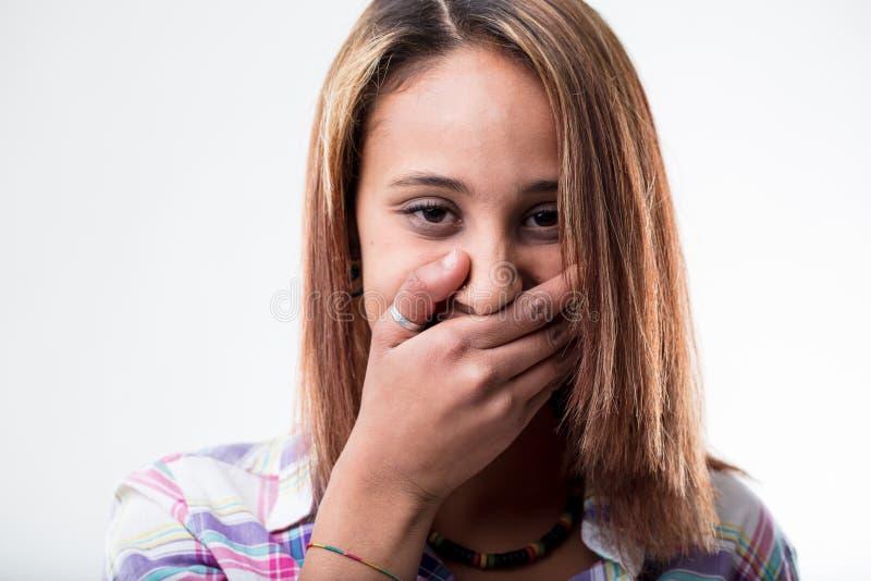 Generad ung kvinna som täcker hennes mun fotografering för bildbyråer