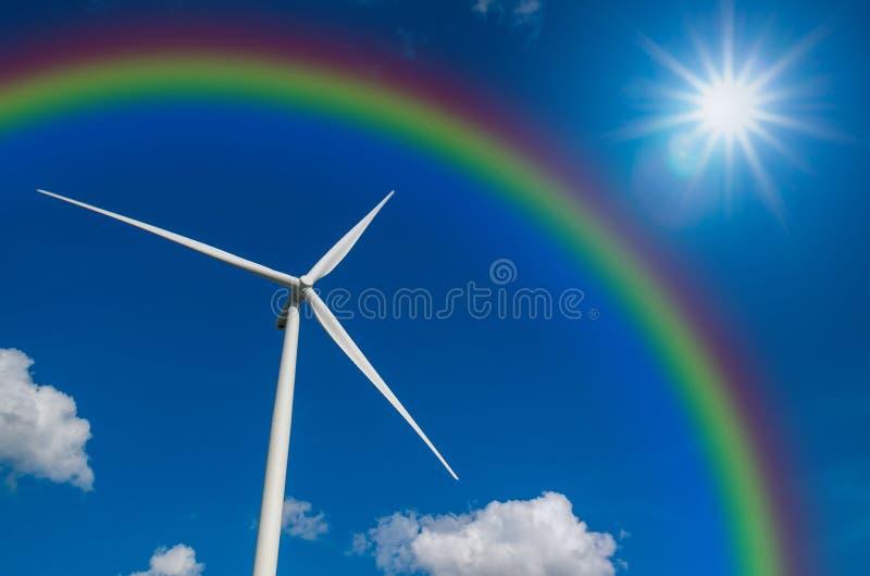 Generador de poder de la turbina de viento del primer con el arco iris en el cielo azul imagen de archivo