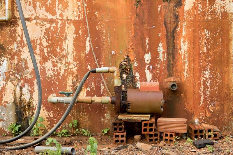Generador de turbina del agua del vintage en el ladrillo mojado viejo - mohoso pelado imagen de archivo