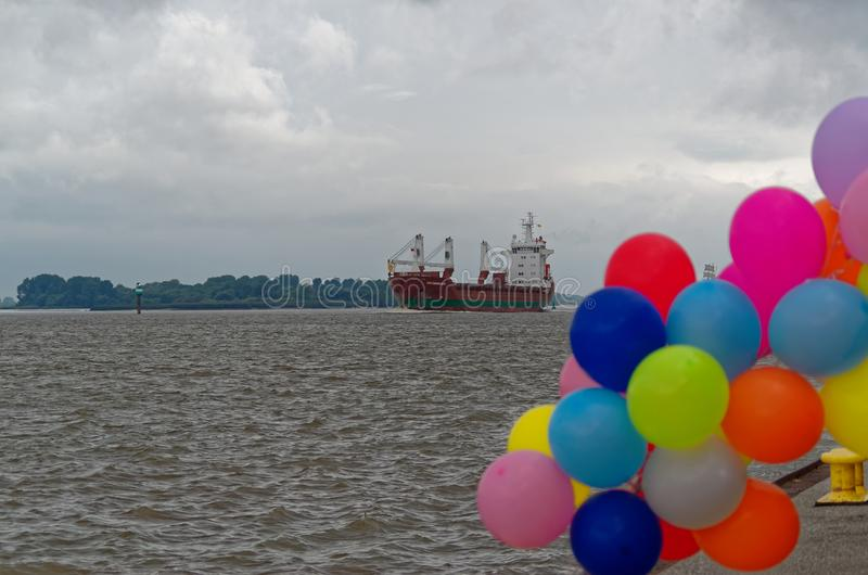 General cargo ship and colorful balloons on quay in foreground. General cargo ship and colorful balloons in foreground, Hamburg Blankenese, Germany royalty free stock photo