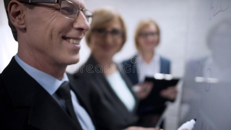 General manager pointing company goals with marker on board, business planning royalty free stock image