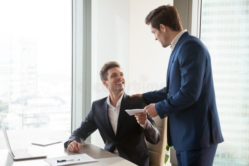 Boss giving money premium to happy employee stock photo