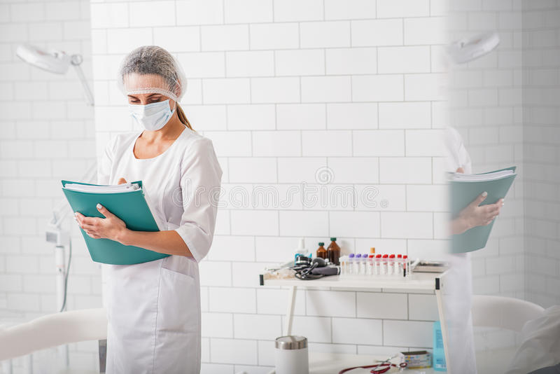 General practitioner writing diagnosis in clinic stock photo