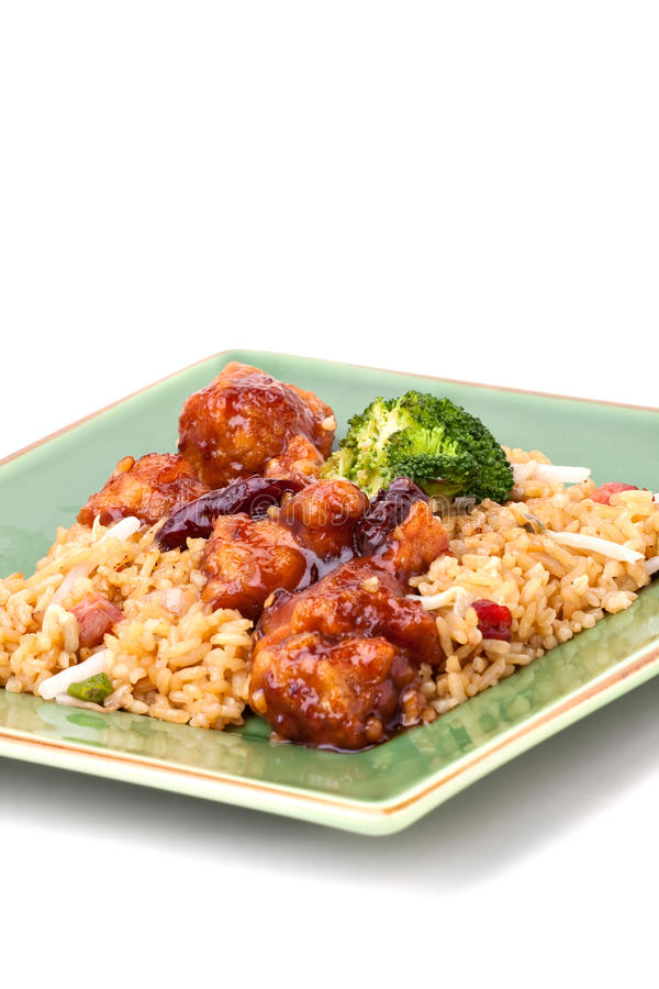 General Tso's Chicken. A plate of General Tsos chicken with broccoli and pork fried rice isolated on a white background royalty free stock photo