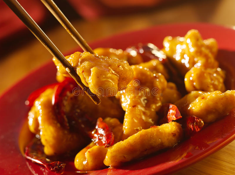 General tso's chicken with chopsticks. Chinese food - Eating general tso's chicken with chopsticks stock photo