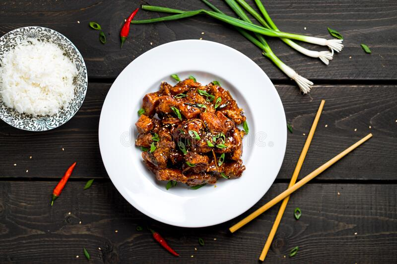 General Tso`s Chicken plate with rice top view. General Tso`s chicken also tsao or tao is a popular chinese restaurant food with deep-fried crispy chicken stock images