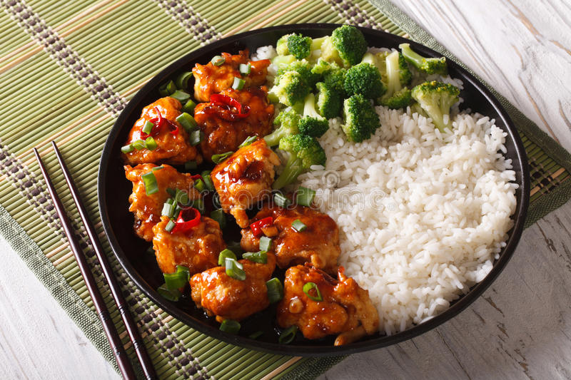 General Tso's chicken with rice, onions and broccoli. horizonta. General Tso's chicken with rice, onions and broccoli close-up on a plate. horizontal stock image
