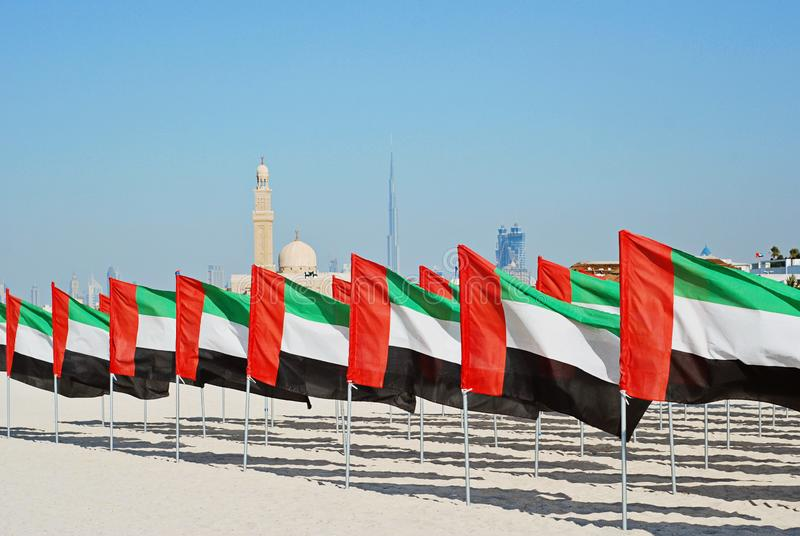 General view of the flags and the mosque in the background. General Dubai city skyline view and lot of United Arab Emirates flags. National Day of the United royalty free stock image