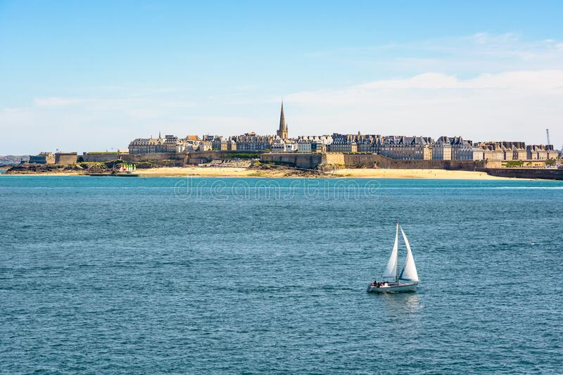General view of the walled city of Saint-Malo in Brittany, France. With the steeple of the cathedral protruding above the buildings behind the wall and a boat royalty free stock image