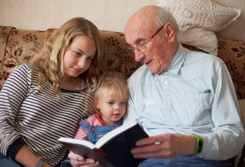 Generaties die een boek lezen stock afbeeldingen