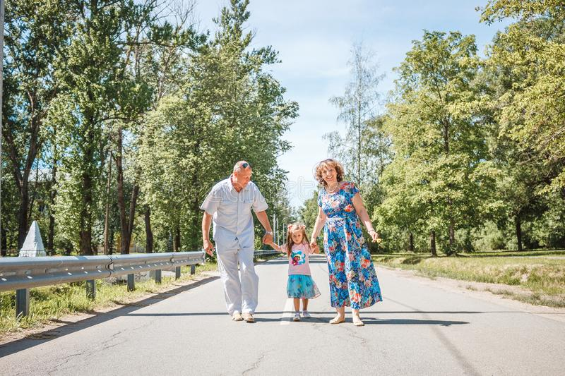 Generation concept - happy smiling grandmother, grandfather and little granddaughter walking at park royalty free stock photo