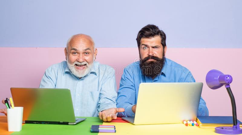 Generation of people and stages of growing up. Senior man using a laptop computer with his son. Senior man using laptop. PC with his adult son stock photography