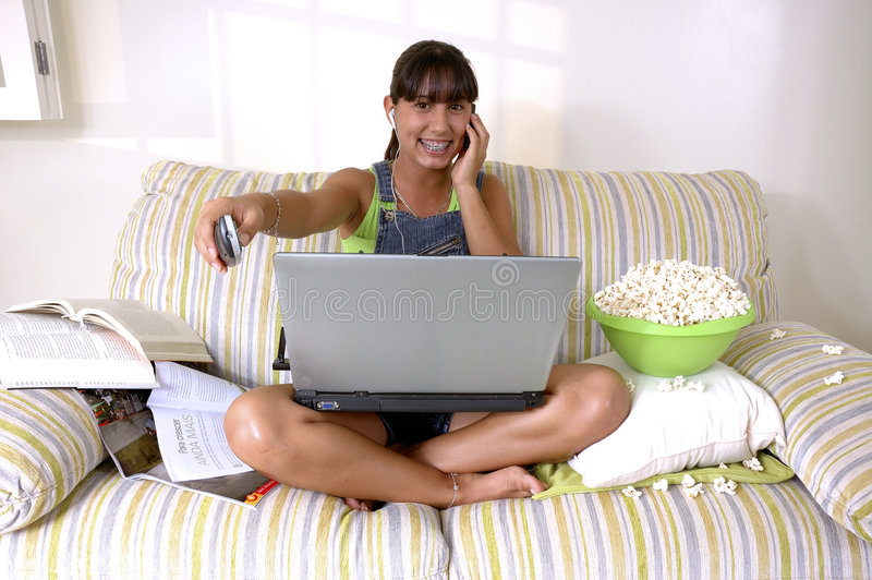 Generation y. Girl of generation Y doing many things at the same time (calling, watching tv, Surfing the web and eating popcorn stock photos
