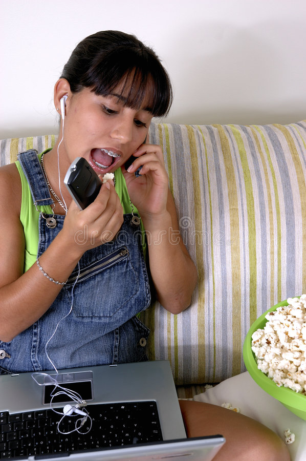 Generation y. Girl of generation Y doing many things at the same time (calling, watching tv, Surfing the web and eating popcorn stock image