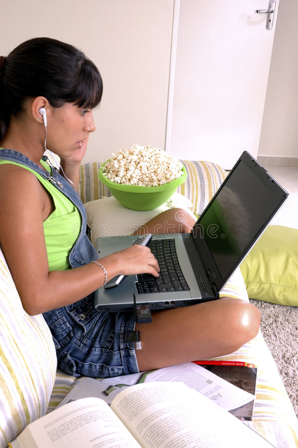 Generation y. Girl of generation Y doing many things at the same time (calling, watching tv, Surfing the web and eating popcorn royalty free stock image
