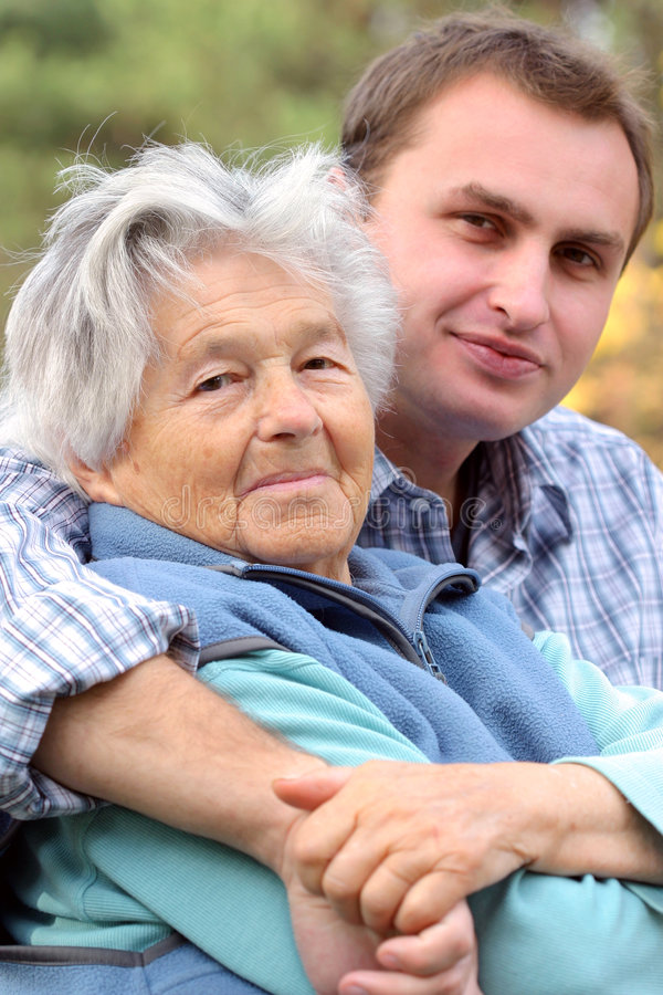 Generations. Woman in her eighties and young man. Focus on woman stock photography